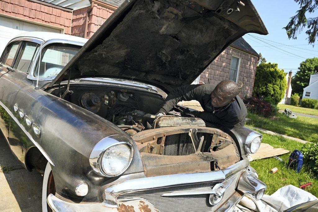 A man fixes a 1956 Buick Super.