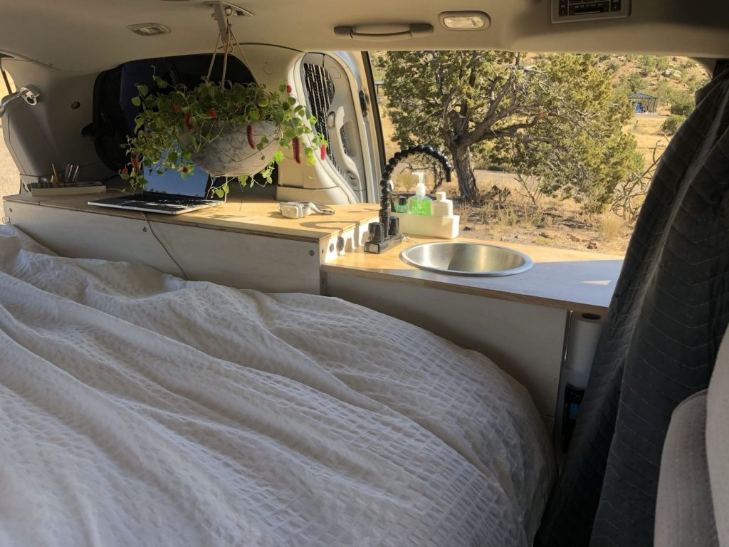 Nissan Quest camper interior with the bed made and a scenic view