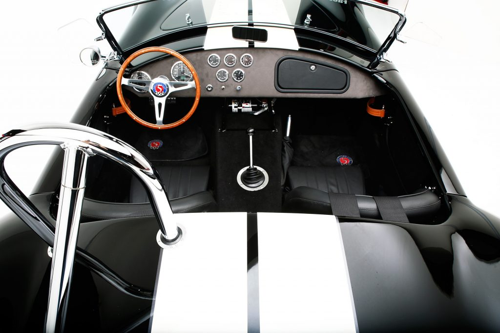 An overhead view of the black interior of a black-with-white-stripes Factory Five Racing Mk4 Roadster Shelby Cobra 427 replica kit car