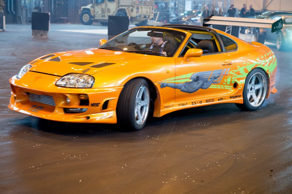 A yellow Toyota Supra coupe performing Fast and Furious Live