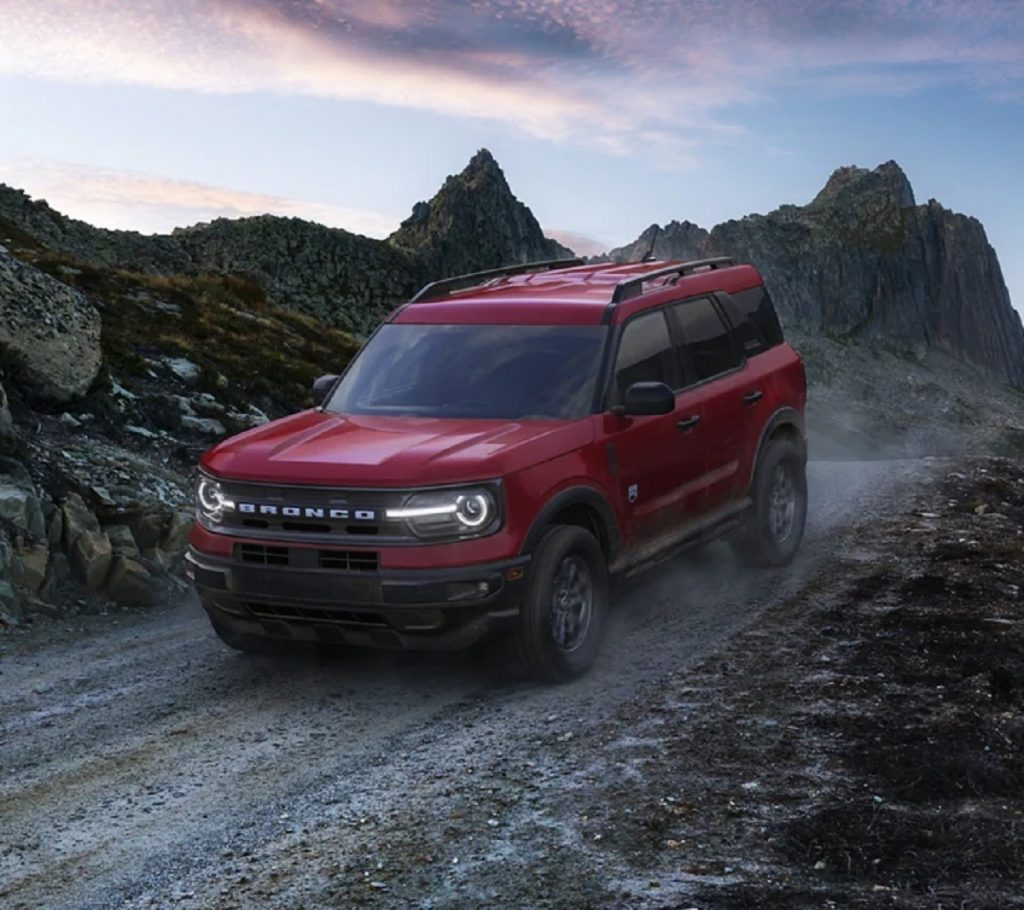 A red 2021 Ford Bronco Sport crossover drives through the mountains.