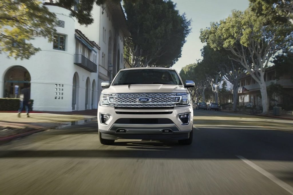 A beige 2021 Ford Expedition races through the city.