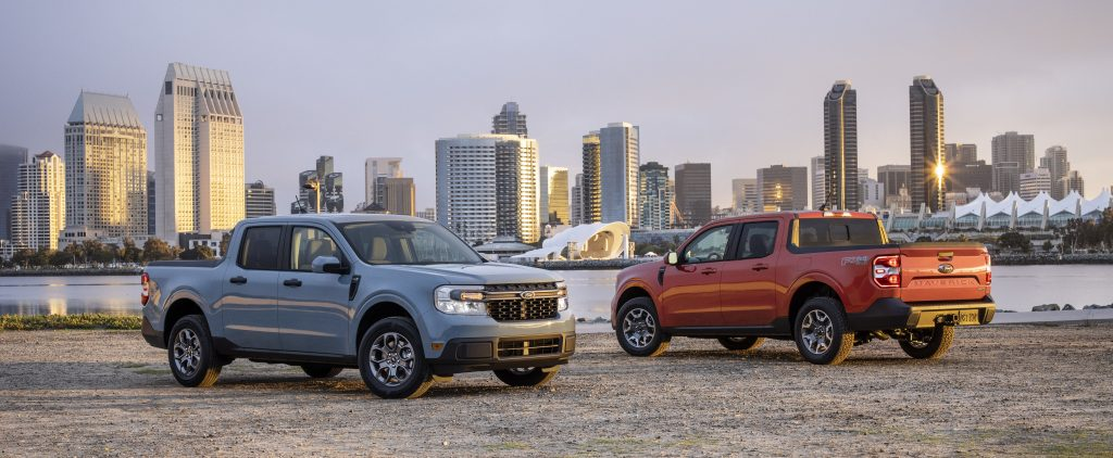 2022 Ford Maverick Hybrid XLT and 2L-EcoBoost AWD Lariat pickup truck pair parked with a skyline view.
