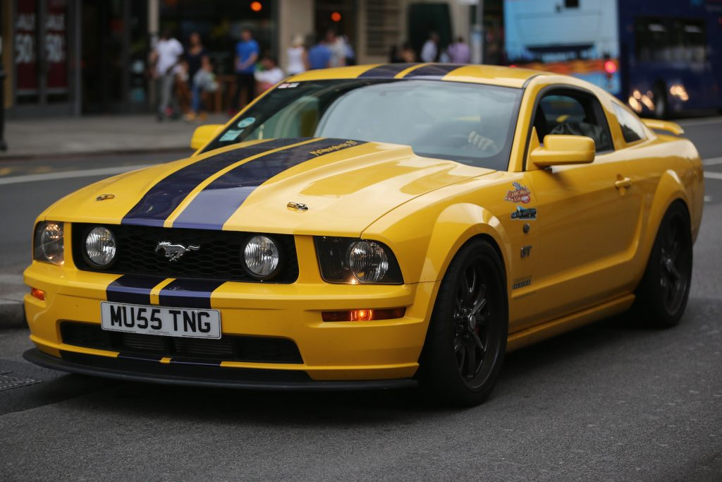 A yellow Ford Mustang on display