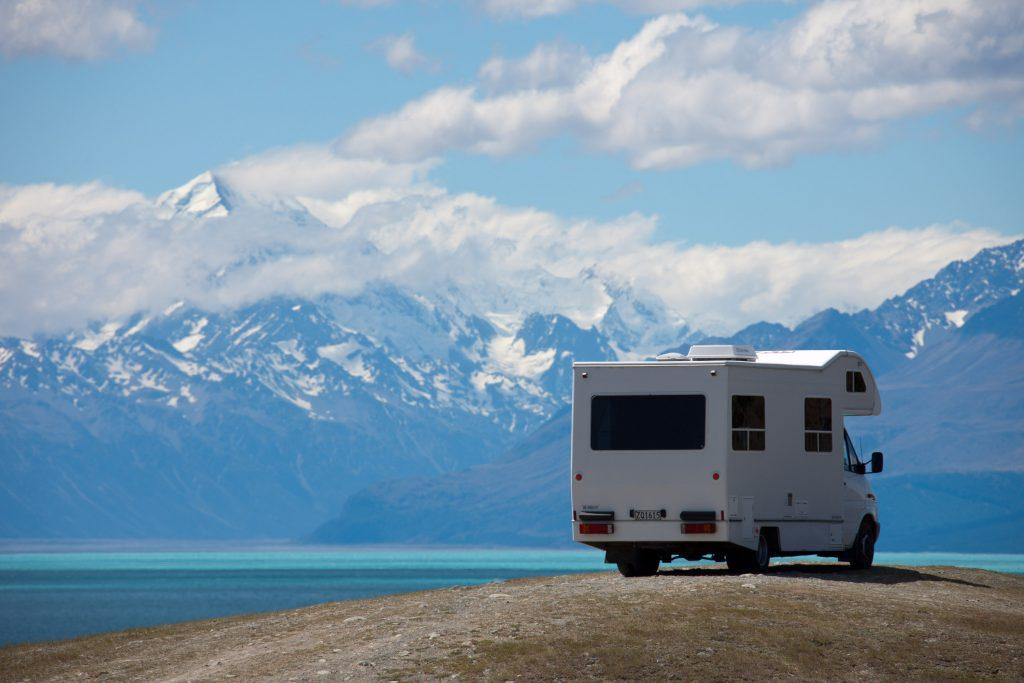 A white RV parked next to a bright blue mountain lake