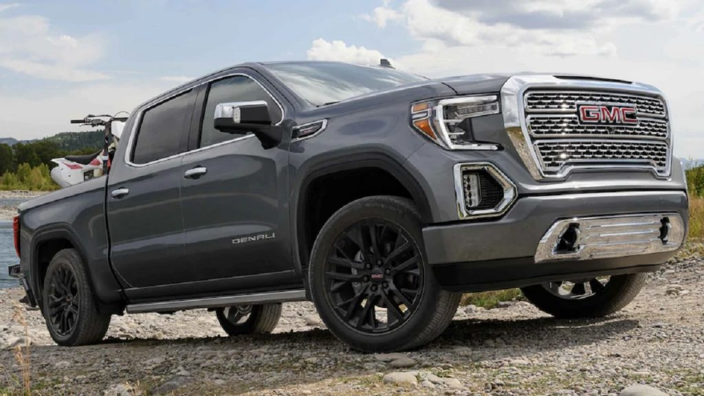 A gray 2021 GMC Sierra 1500 drives up a gravel hill. The Sierra is one of the pickups with the worst headlights.