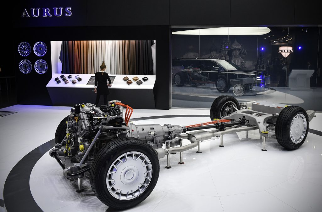 The rear-wheel drive chassis of a car on display, complete with engine