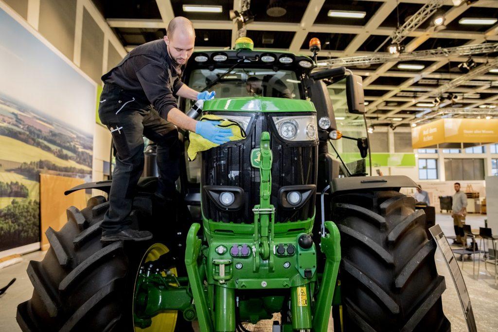 a John Deere technician wiping down the front end of a John Deere tractor