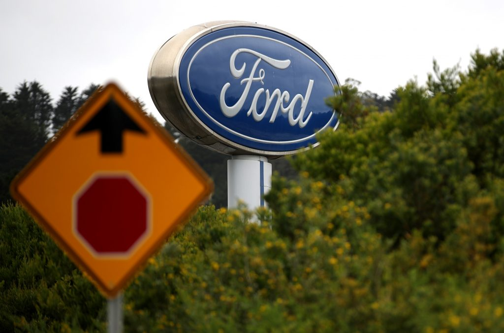 A gigantic Ford dealership sign with a stop sign in the foreground