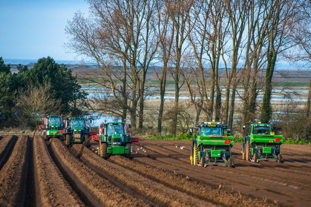five green John Deere tractors preparing a large field for planting