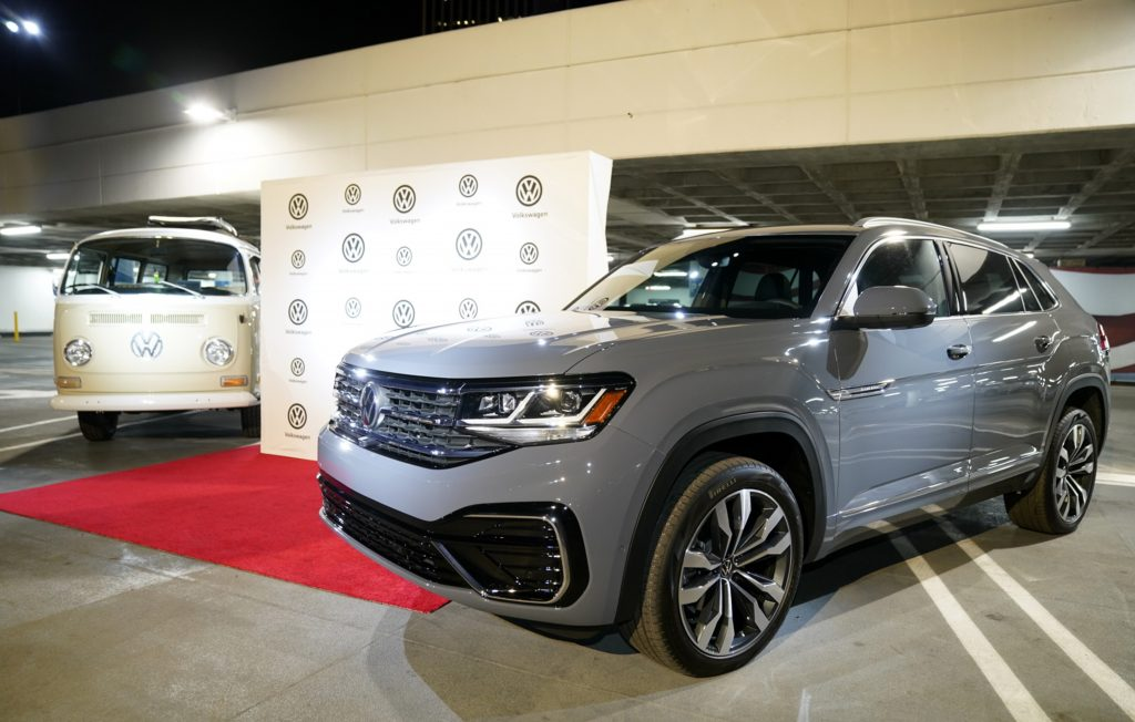 a gray Volkswagen Atlas on display at a show next to a new VW type 2 electrified bus