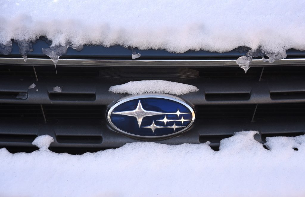 Subaru's logo on the hood of a car covered in snow