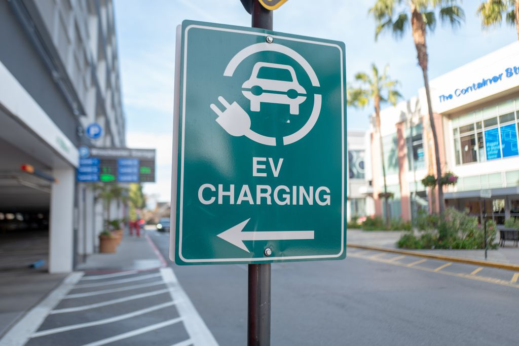 A green sign with white text indicating EV charging availability.