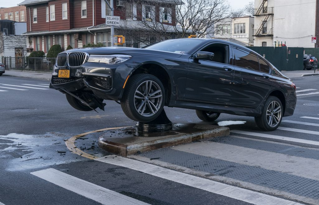 A wrecked BMW sitting on top of a parking bollard in a freak accident