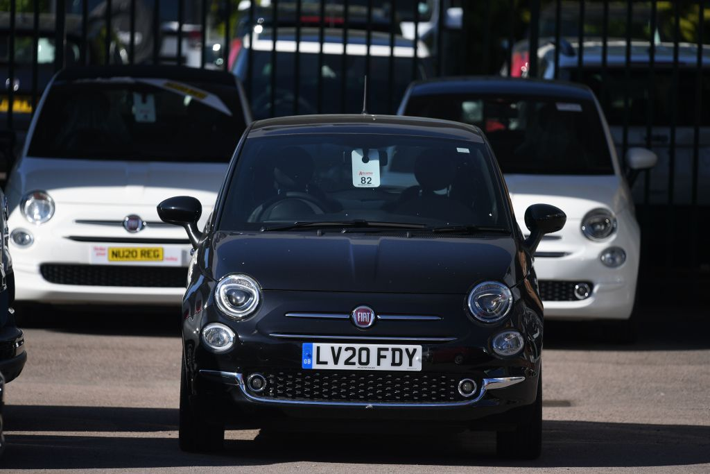 A gas-powered black Fiat 500 with other 500 models in
