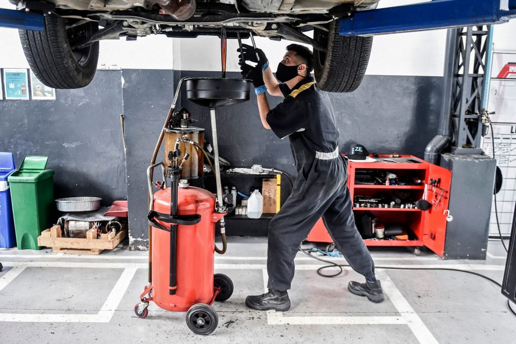 A mechanic performs an oil change in a shop