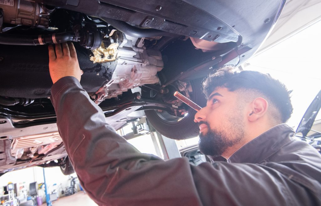 A mechanic inspects the transmission of a car, often a point of inspection during a pre-purchase inspection