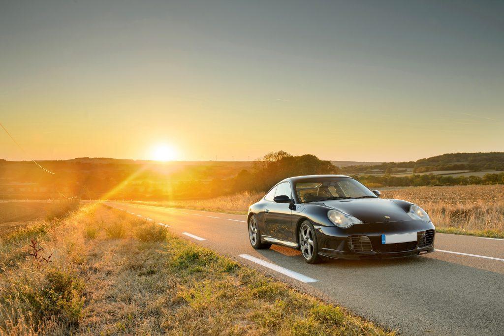 A black Porsche 911 photographed at sunset