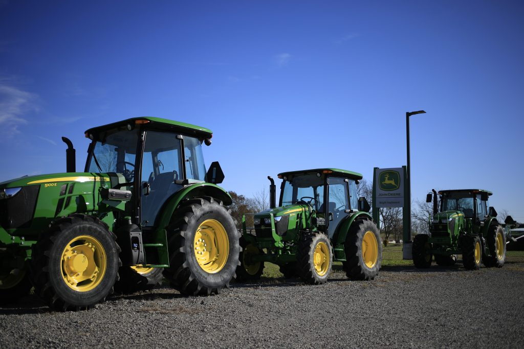 a lineup of green John Deere tractors at a dealership in front of a John Deere sign