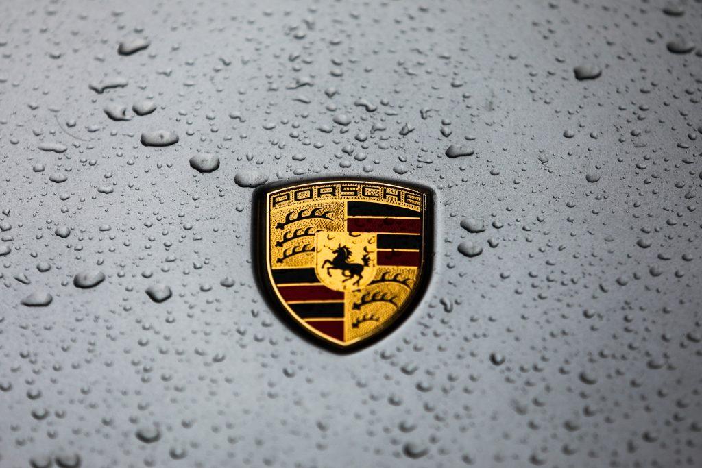 A Porsche badge, wet from the rain