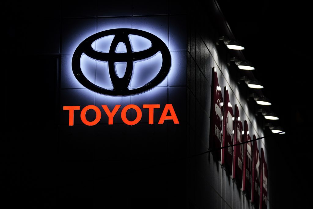 The Toyota logo at night on a building in Japan
