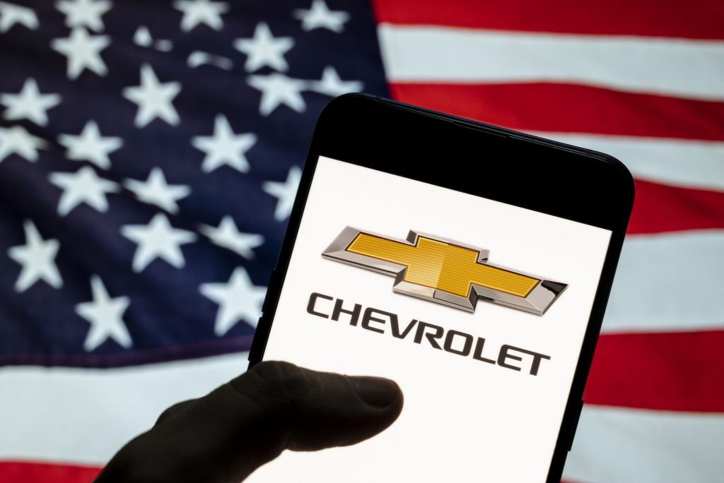 Chevrolet logo seen displayed on a smartphone with a flag of the United States in the background