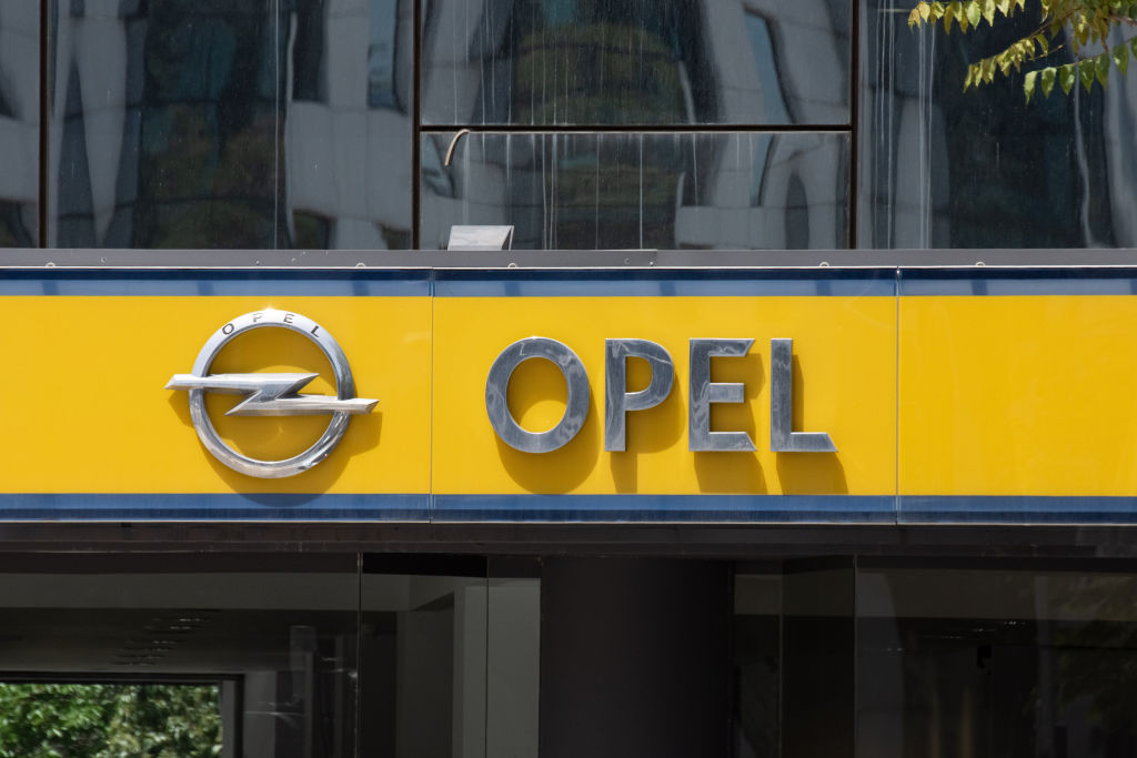 The logo of Opel hangs above a dealership on a yellow background