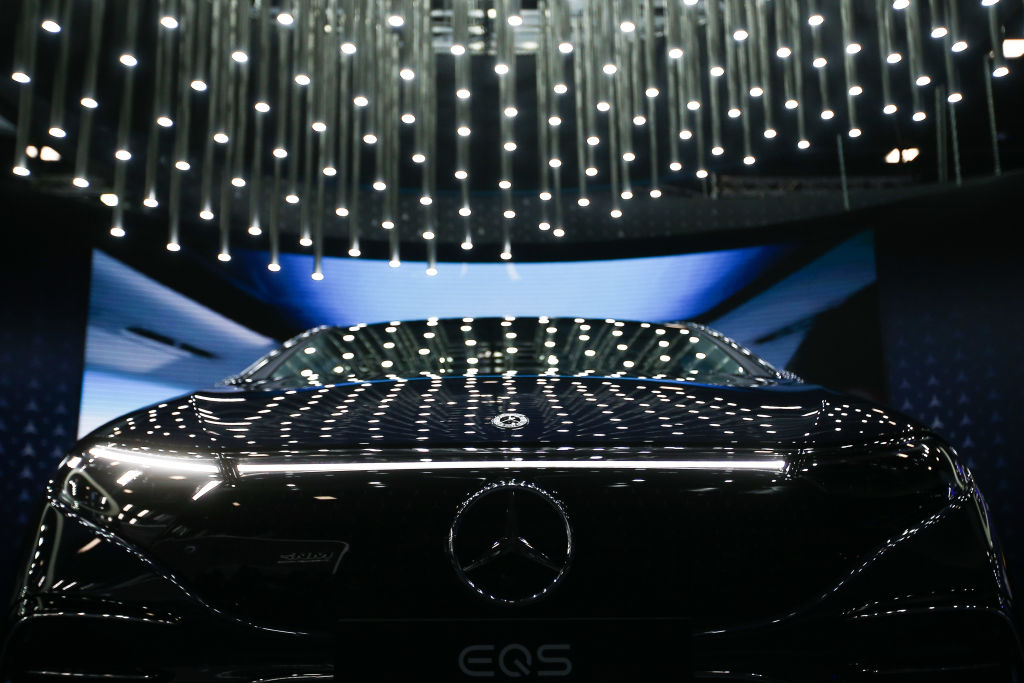 The new electric Mercedes EQS with string lights reflecting off the dark blue paint