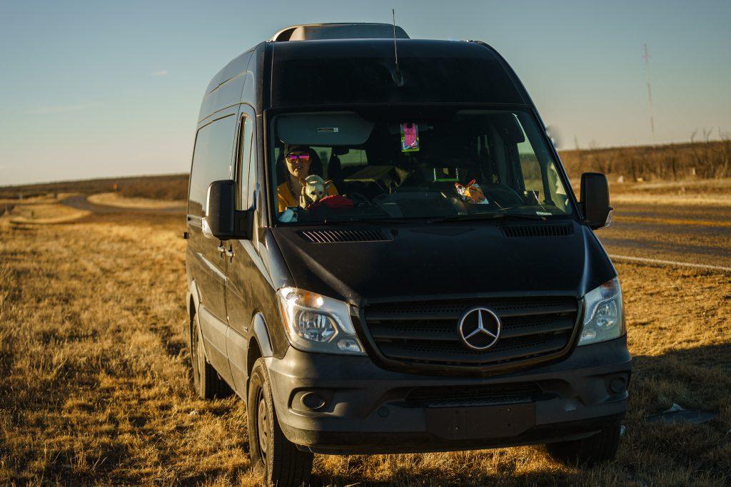a black Mercedes Sprinter camper van driving off-road