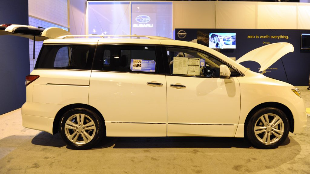 a white 2012 Nissan Quest minivan on display at an auto show