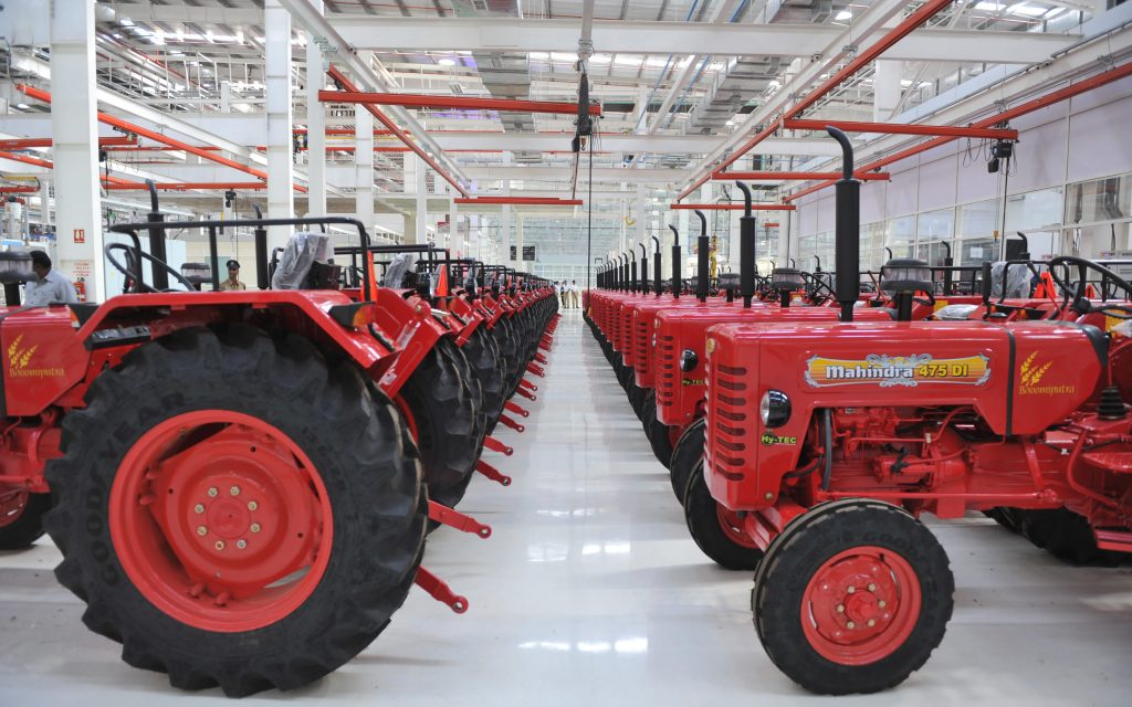 a line of red Mahindra Tractors fresh off the line in a manufacturing facility