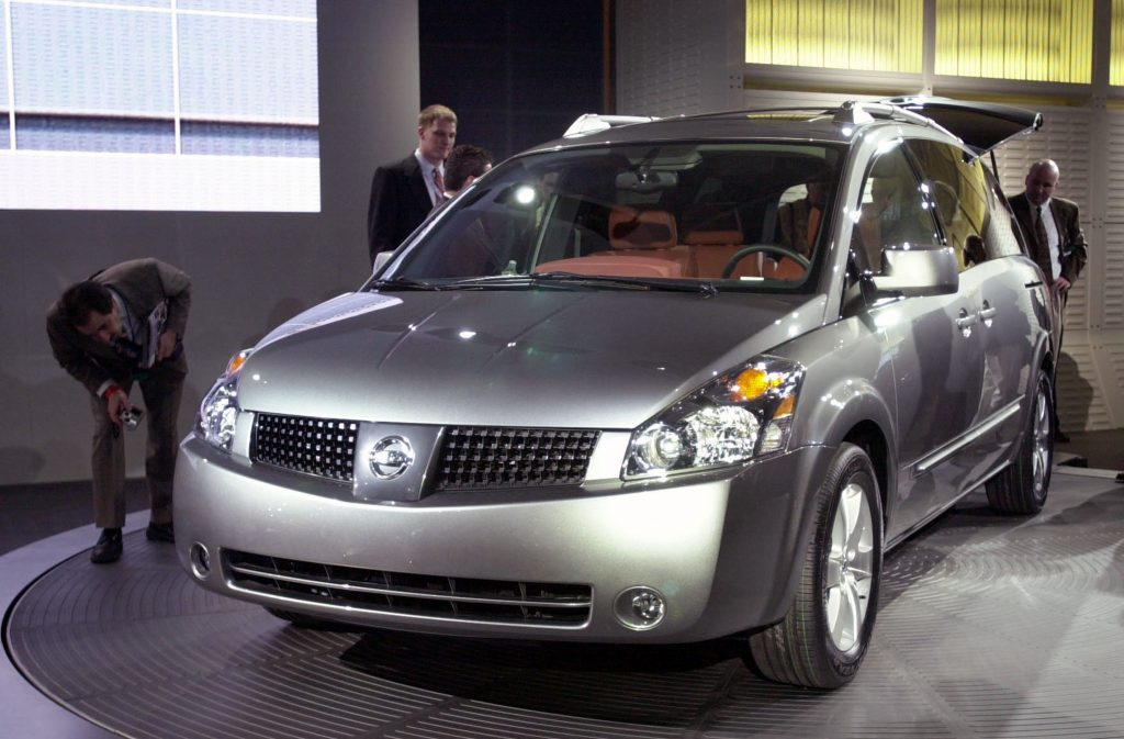 a silver Nissan Quest minivan model at an auto show on display