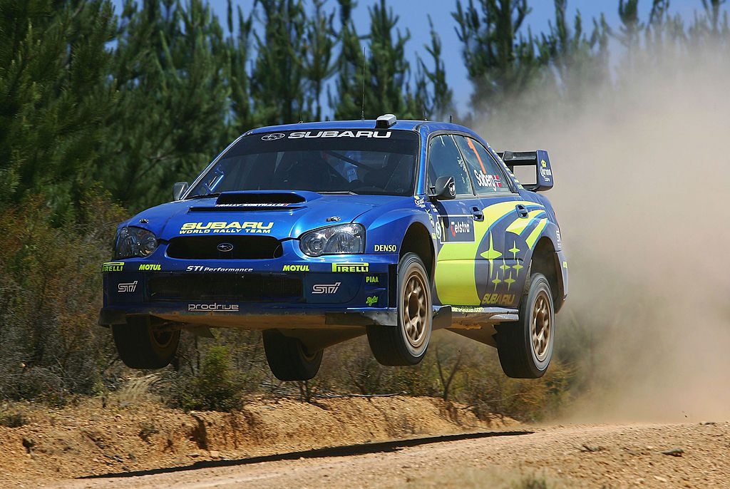 The blue and yellow Subaru WRX rally car airborne in Perth