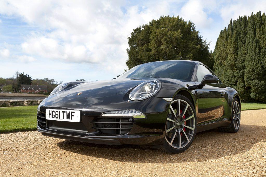 A black Porsche 911 sits on a gravel driveway