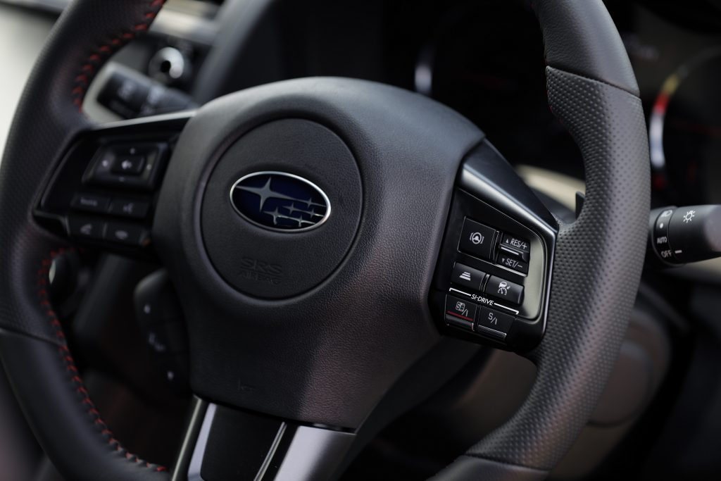 The leather-wrapped, red-stitched steering wheel of a Subaru WRX