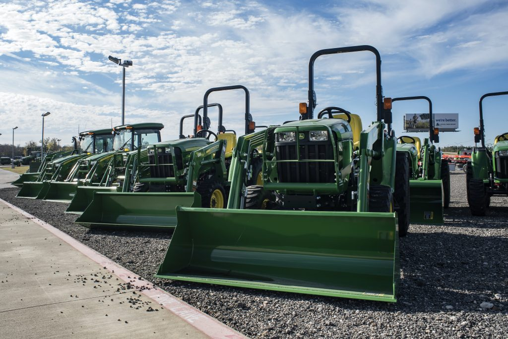 green John Deere tractors on display at an agriculture expo.