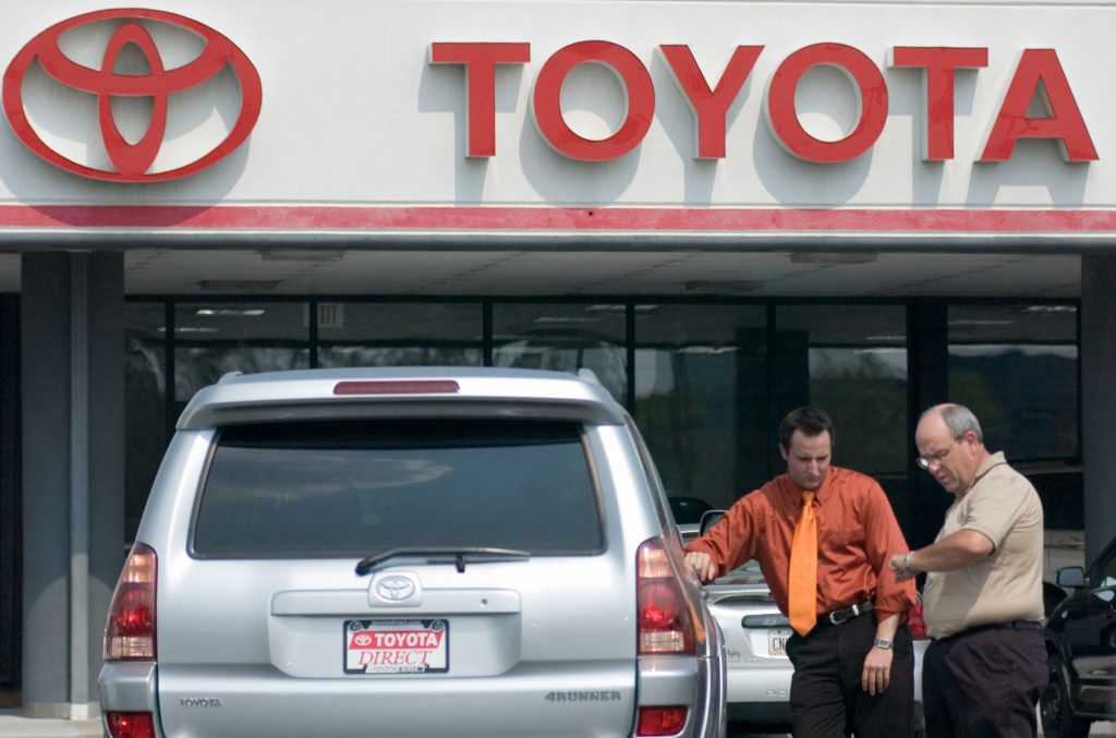 Two men talk at a Toyota used car lot next to a 4Runner