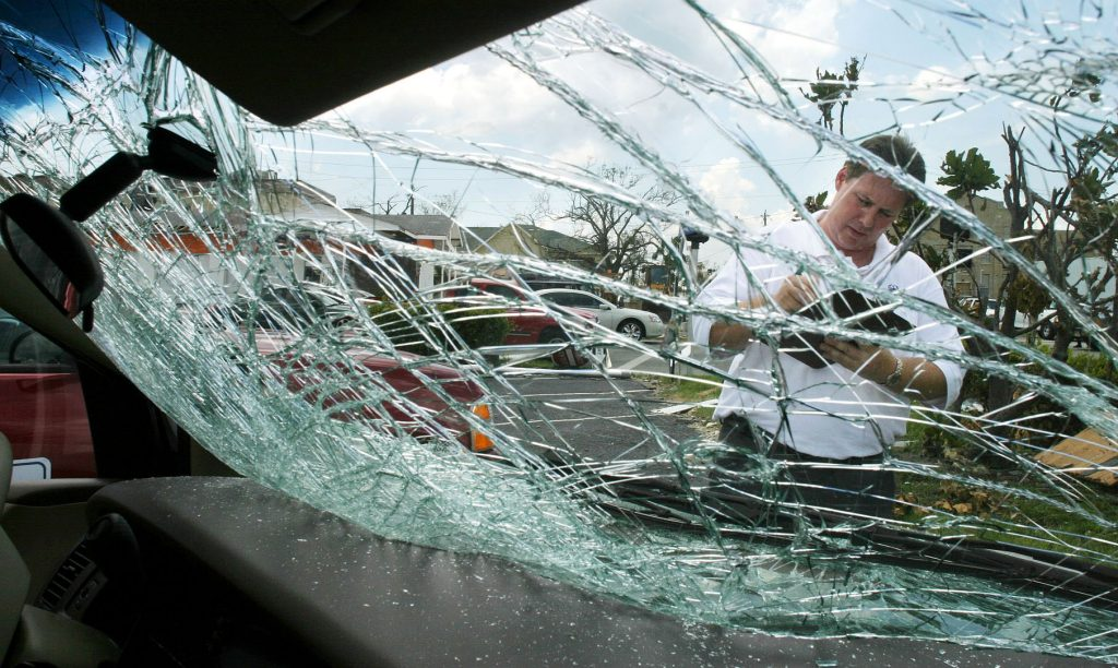 An insurance adjuster views a broken windshield.