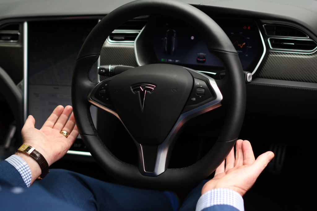 A man removes his hands from the steering wheel of a Tesla on Autopilot