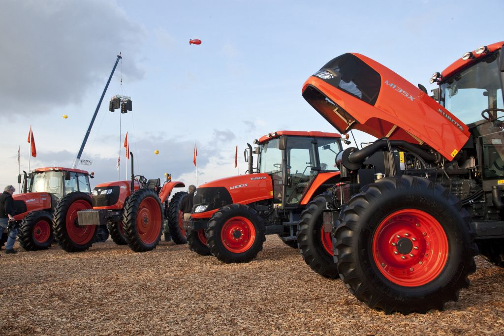 an array of Kubota tractor models are on display at an agriculture expo in California