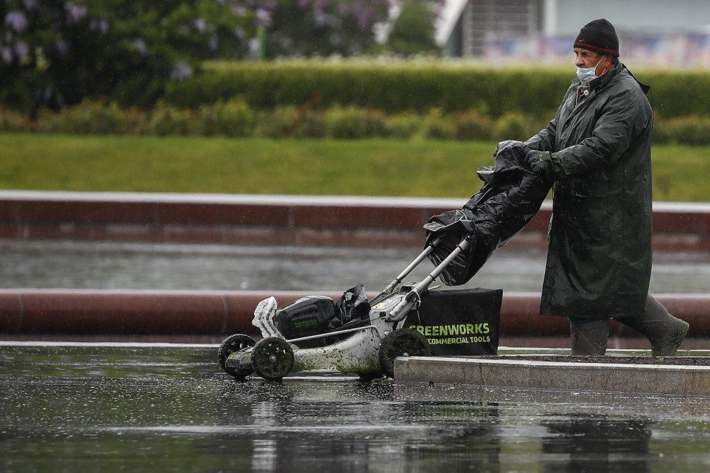 A man using a Greenworks electric push lawn mower. Greenworks makes one of the best electric push lawn mowers, according to Bob Vila