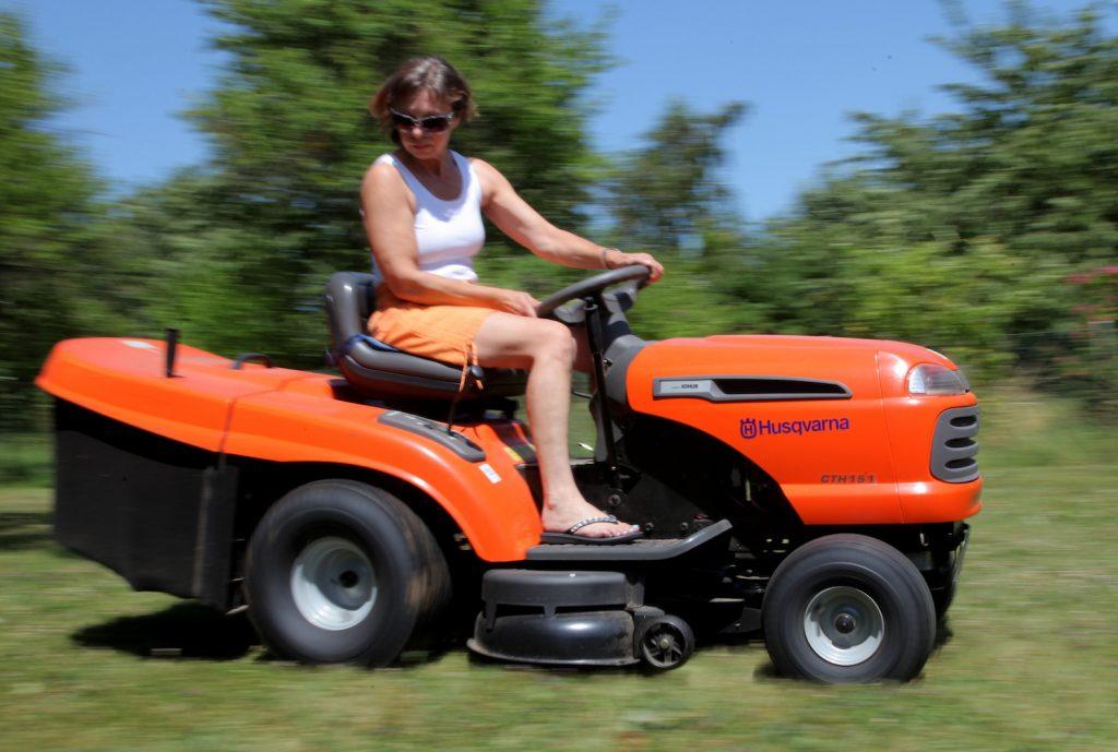 A woman on a Husqvarna riding lawn mower