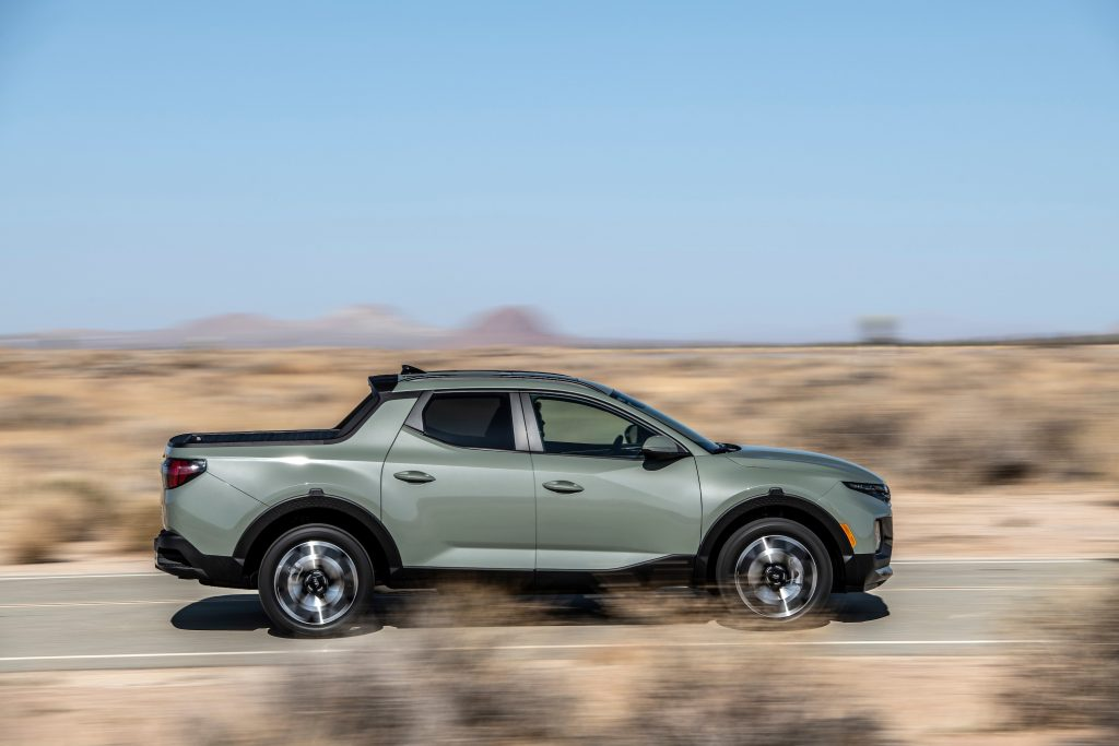 The 2022 Hyundai Santa Cruz in a gray color driving along the road in the desert