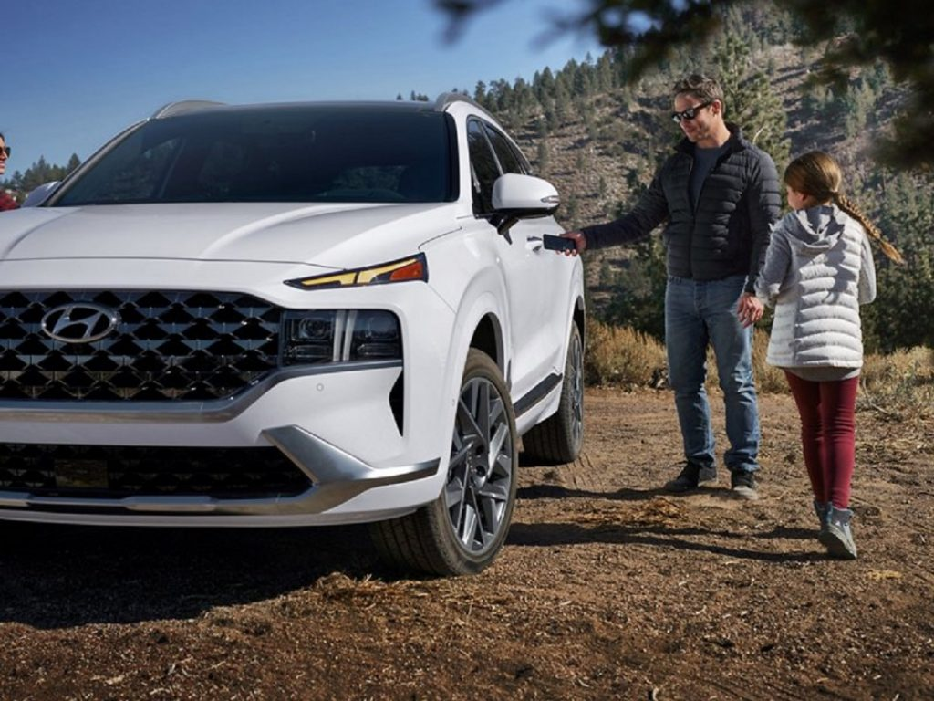 A man and his daughter are getting into a 2021 white Hyundai Santa Fe.