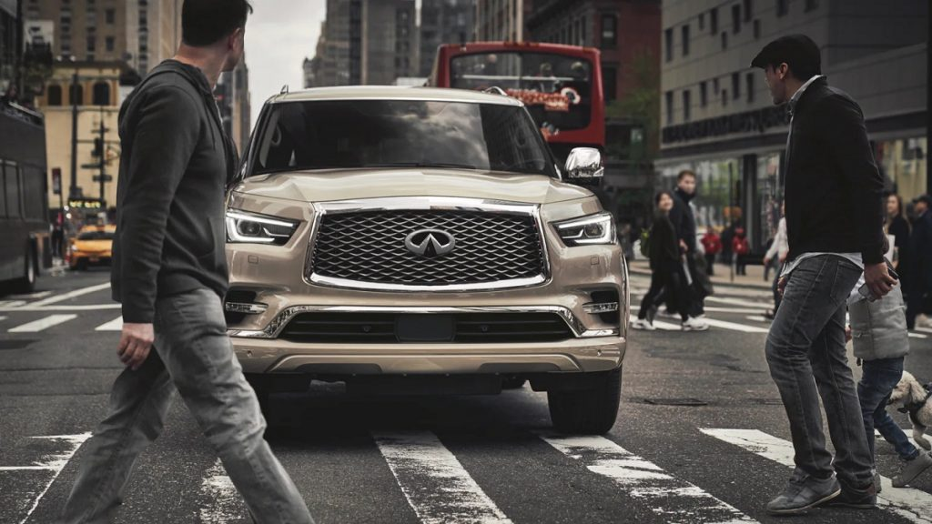 A beige 2021 Infiniti QX80 stopped at a crosswalk as pedestrians walk in front of it.
