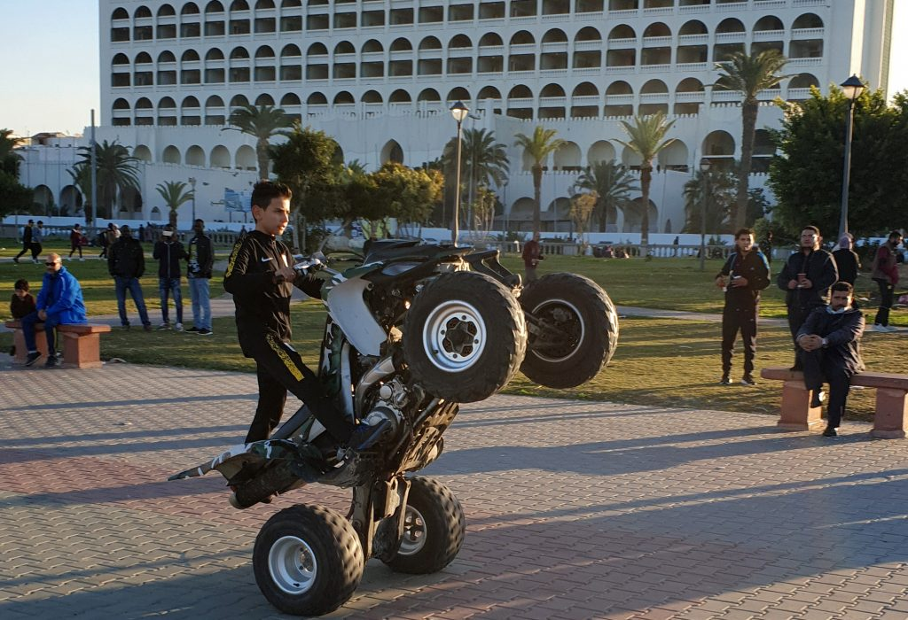 """A Libyan boy performs a wheelstand (""""wheelie"""") maneuver with an all-terrain vehicle (ATV) at a park in the capital Tripoli near the Martyrs' Square"""