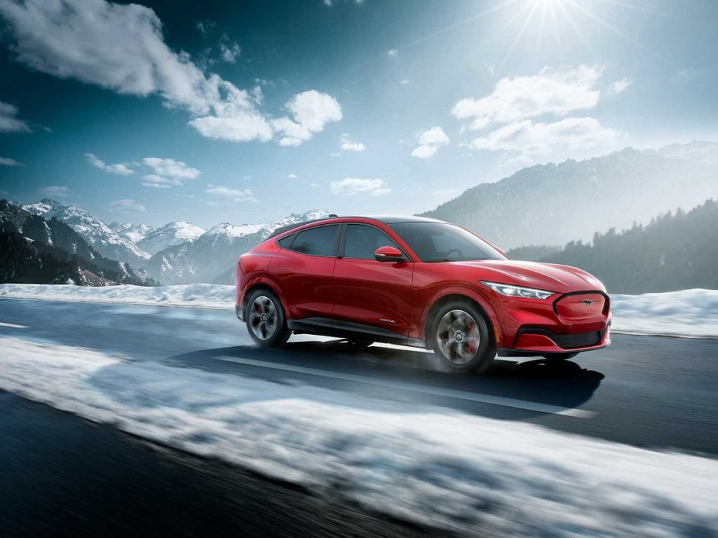 A red 2021 Ford Mustang Mach-E drives down a snow-lined road.