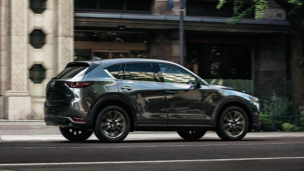 A dark colored Mazda CS-5 drives through a city.