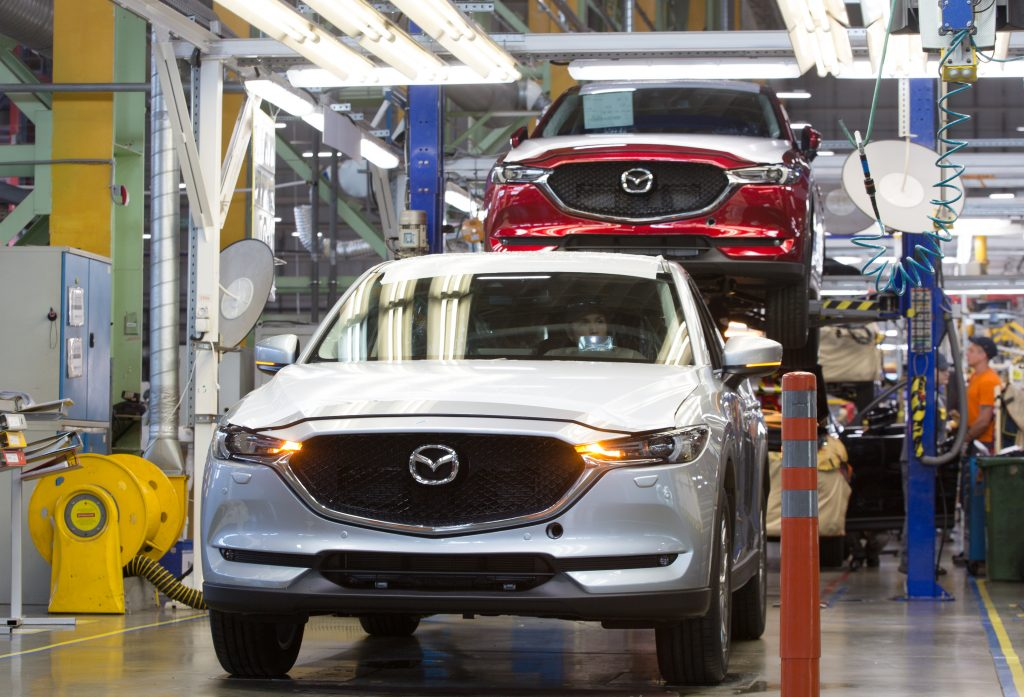 A worker drives a Mazda Motor Corp. CX-5 sports utility vehicle (SUV) on the assembly line at the Mazda Sollers Manufacturing Rus LLC plant