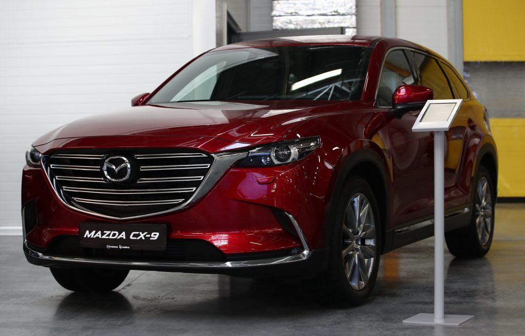 A red Mazda CX-9 SUV on display at a Mazda Sollers Manufacturing car factory during a visit by the president of Russia and the prime minister of Japan